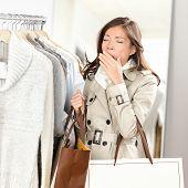 Mulher cansada bocejando fazer compras de roupas