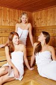 Three attractive women chatting relaxed in a sauna