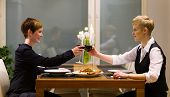 picture of lesbian  - Happy lesbian couple sits on a dinner table and having good time together - JPG