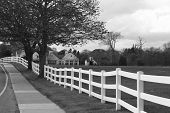 stock photo of pasture  - white fence surrounding a horse pasture with home and barn in the distance in black and white - JPG