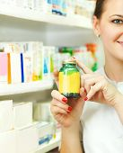 Closeup Of A Blurred Female Pharmacist Holding Out Tablets In Bottle