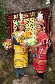 picture of ifugao  - Two beautiful Filipino women dress in traditional Ifugao clothing of bright yellow and red woven patterns at Mines View Park in Bagio City Luzon Philippines - JPG