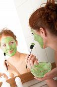 Постер, плакат: Уход за серии молодая женщина применяя зеленые маска для тела