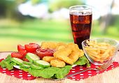 Fried chicken nuggets with french fries,cola,vegetables and sauce on table in park