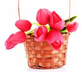 Bouquet of beautiful artificial flowers in wicker basket, isolated on white