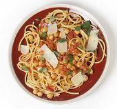 Spaghetti with a chickpea, tomato and chilli flakes sauce, garnished with fresh torn basil leaves and flakes of parmesan. This is a traditional Italian dish, called spaghetti alla ceci