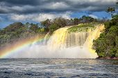 stock photo of canaima  - powerful waterfall and a rainbow in front shot in canaima - JPG