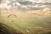 stock photo of glider  - Air view to the paraglider in Andes mountain in the soft sunset light with an awesome view to mountains - JPG