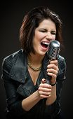 Half-length portrait of female rock singer wearing black jacket and keeping microphone on grey backg