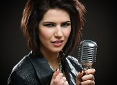 Portrait of female rock singer wearing black jacket and keeping microphone on grey background. Concept of music and rave