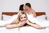 stock photo of cheater  - Cheeky young woman in a threesome or the cheating partner in an affair peeking out of the bottom of the bedclothes with a saucy expression as a young couple at the top of the bed share a loving kiss - JPG
