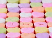 Closeup of the words I Love You spelled out on candy hearts.  The hearts are arranged in straight ro