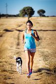 Woman And Dog Running In Rural Countryside Path
