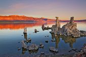 The magic of Mono Lake. Outliers -calcareous tufa formation on the smooth water of the lake. Orange