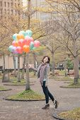 Young woman playing and holding balloons at park in Taipei, Taiwan, Asia.