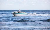 stock photo of outboard  - Man driving a fast boat  - JPG