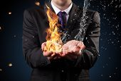 Businessman with fire and water in hands. Concept of threats and solutions as so as manager responsibility and power