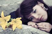 stock photo of tombstone  - Sad young woman lying on the tombstone - JPG