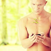 Muscular man holding small plant and soil in his hands.