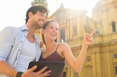 Man and woman or young couple making trip as tourists in Munich at the Odeon Church with city map on