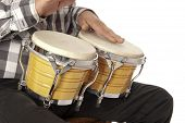 stock photo of bongo  - Male figure playing and drumming on yellow bongo on his lap - JPG