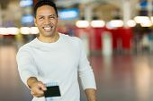 picture of over counter  - handsome mature man handing over air ticket at check in counter - JPG