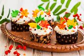 Homemade cupcakes decorated with cream and sugar autumn leaves