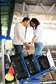 caring man comforting his girlfriend before boarding airplane at air port