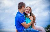 romantic couple eating ice cream at park