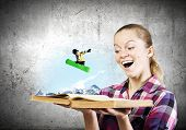 Young woman looking in opened book and snowboarder making jump