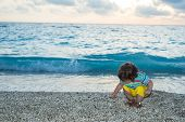 Toddler Boy Collect Pebbles At Sea