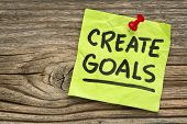 create goals reminder - handwriting on a green sticky note against grained and knotted wood board