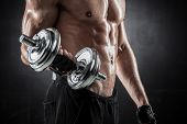 foto of arm muscle  - Brutal athletic man pumping up muscles with dumbbells - JPG