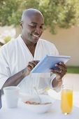 Handsome man in bathrobe using tablet at breakfast outside on a sunny day