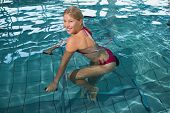 picture of day care center  - Fit happy blonde using underwater exercise bike in swimming pool at the leisure centre - JPG