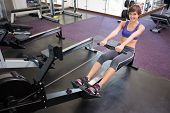 Fit smiling brunette working out on rowing machine at the gym