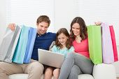 Family Of With Shopping Bags Using Laptop