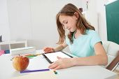Girl Using Digital Tablet In Study Room