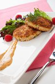 picture of crab-cakes  - Two crab cakes appetizer garnished with spicy sauce green salad and raspbery - JPG