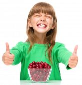 Cute girl is eating cherries and showing thumb up sigh, isolated over white