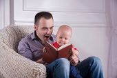 Father and toddler son sitting in armchair reading a book