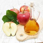 stock photo of cider apples  - Apple cider vinegar and fresh apple on a wooden background - JPG