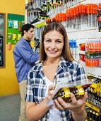 Portrait of female customer scanning product through mobile phone with man in background at hardware store