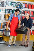 Full length of young salesman assisting senior man in selecting toolbox at hardware store