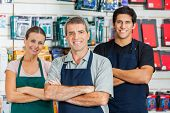 Portrait of smiling salespeople standing arms crossed in hardware shop