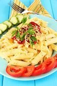 Rigatoni pasta dish with tomato sauce on blue wooden table