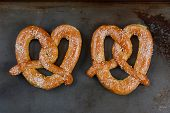 Two large Sourdough pretzels on a metal baking sheet. The salted snacks are side by side in horizontal format.