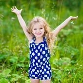 Cute Smiling Little Girl With Long Blond Curly Hair And Flower In Her Hands. Girl With Raised Hands.