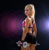 fitness, exercising and dieting concept - sporty woman with heavy steel dumbbells from back