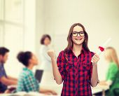 university and education concept - smiling female student in eyeglasses with diploma